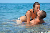 Young hot woman sitting astride man in sea near coast, man and — Stock Photo