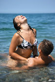 Young hot woman sitting astride man in sea near coast — Stock Photo
