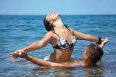 Young hot woman sitting astride man in sea near coast, Having jo — Stock Photo