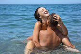 Young hot woman sitting astride man in sea near coast, closed ey — Stock Photo
