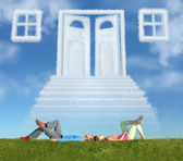 Lying couple on grass and dream door way collage — Stock Photo
