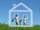 Family with boy on meadow and dream cloud house collage — Stock Photo