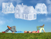 Lying couple on grass and dream three cloud houses collage — 图库照片