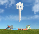 Lying couple on grass and dream house key collage — Stock Photo
