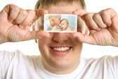 Man with card of kids on eyes, collage — Stock Photo