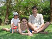 Famili sitzend gras — Stockfoto