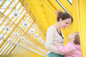 Mother with baby on yellow bridge — Стоковое фото