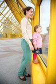 Young woman with baby on pedestrain bridge — Stok fotoğraf