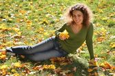 Woman with the yellow leaf sits on the grass — Stock Photo