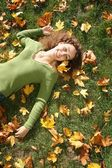 Frau mit dem gelben blatt liegt auf dem rasen — Stockfoto