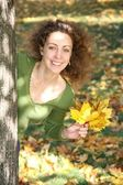 Woman with the yellow leaf looks of the tree — Stock Photo