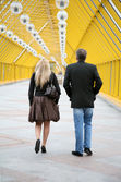 Couple on pedestrian bridge — Stock Photo