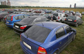 The stand of automobiles on to the meadow — Stock Photo