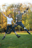 Young roller couple jump — Stock Photo