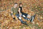 Young roller couple sit on yellow leaves — Stock Photo