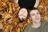 年轻夫妇说谎黄色树叶上 — 图库照片