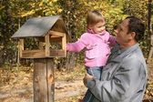 Grandfather with the granddaughter in the park in autumn — Stock Photo