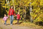 Mother with the children goes for a walk in the park in autumn — Stock Photo