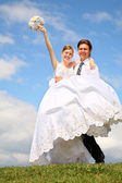 Fiance holds bride on the hands on to the meadow — Foto Stock