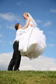 Fiance raises bride on the hands on to the meadow — Foto Stock