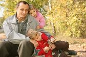Grandfather with the grandson and the granddaughter in the park in autumn — Stock Photo