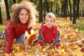 Mother with child on maple leaves — Stock Photo