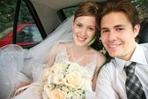 Fiance and bride sit in the automobile — Stock Photo