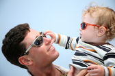 Father with the child in the sunglasses against the background of the sky — 图库照片