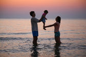 Mummy with daddy and child in sea on sunset — Stock Photo