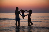 Father with mother hold child in sea on sunset — Stock Photo