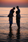 Two men in sea with children on shoulders on sunset — Stock Photo