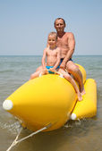 Grandfather with the grandson they sit on the inflatable boat — Stock Photo