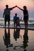 Mother with children and grandfather ashore on sunset — Stock Photo