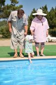 Elderly pair with the granddaughter aside of pool — Stock Photo