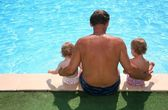 Grandfather with granddaughters seats aboard of pool — Stock Photo