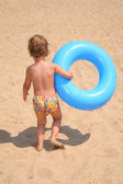 The girl with a lifebuoy ring goes on sand — Stock Photo