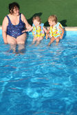 The grandmother and children sit at pool. — Stock Photo