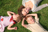 Mother and children lie on the grass — Stock Photo