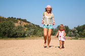 Mother and daughter run on the beach — Stock Photo