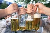 Four hands with the bottles of the beer — Stock Photo
