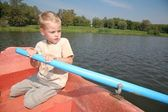 Boy in the boat with the oar — Stock Photo
