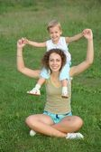Daughter sits on the shoulders in mother on to the meadow — Stock Photo