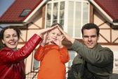 Young family and house — Stock Photo