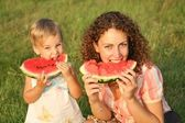 Mother and daughter eat watermelon on the grass — Stock Photo