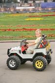 Boy in toy car in park — Stockfoto