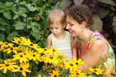 Mother and daughter look on flowers — Stock Photo