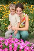 Mother and son look on flowers — Stock Photo