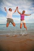 Hombre y mujer saltan por encima del mar — Foto de Stock