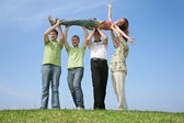 Four friends have lifted the girl upwards — Stock Photo