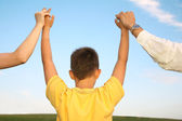 Child, who holds for the hands of parents against the background of the sky — Stock Photo